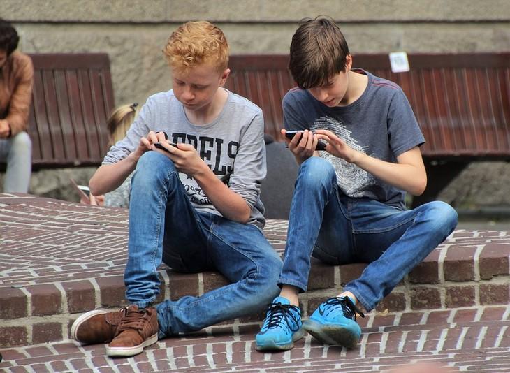 איך לגרום לילדים להפחית את זמני המסך: שני נערים יושבים על שפת מדרכה ומשחקים בטלפונים שלהם