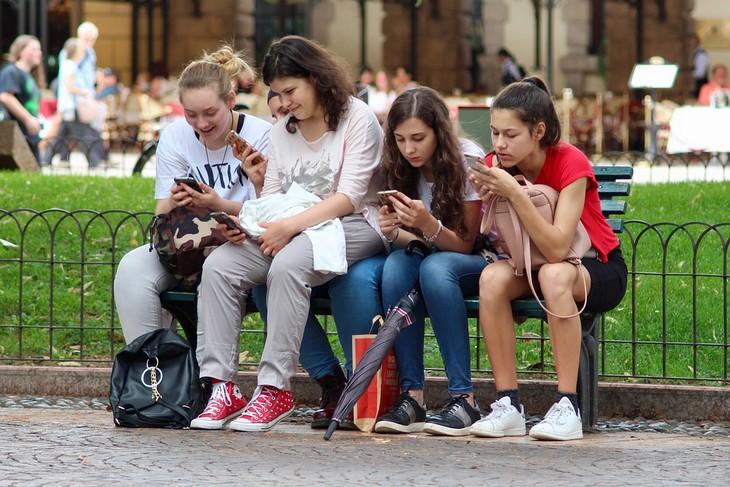 איך לגרום לילדים להפחית את זמני המסך: ארבע נערות יושבות על ספסל ומשחקות בטלפונים שלהן