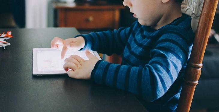 איך לגרום לילדים להפחית את זמני המסך: ילד קטן יושב לצד שולחן ומשחק בטאבלט