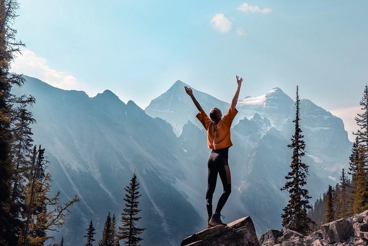 איך לשפר מסוגלות עצמית: אישה עומדת על סלע ומרימה את ידיה לאוויר