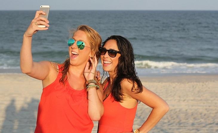 מדריך לשימוש באפליקציית FaceApp: נשים מצטלמות על חוף הים