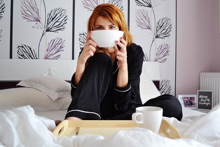 איך לשפר מסוגלות עצמית: אישה יושבת במיטה ומחזיקה מול פניה קערה
