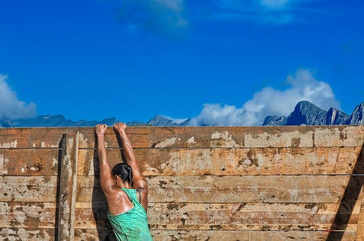 איך לשפר מסוגלות עצמית: אישה נתלית על קיר עץ