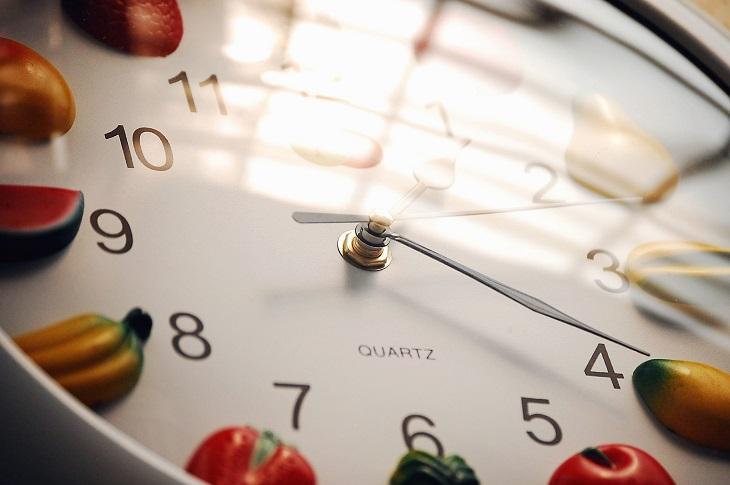מאכלים שלא כדאי לאכול בזמנים מסוימים של היום: שעון שליד ספרותיו מופיעים פירות שונים
