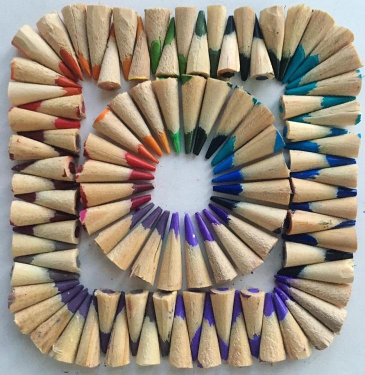 יצירות אמנות צבעוניות מאביזרים ומאוכל: ריבוע ובתוכו עיגול העשויים מחודים של עפרונות צבעוניים