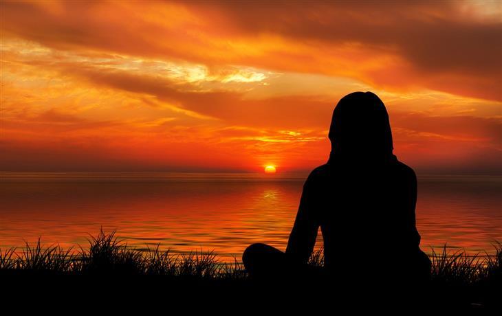 התבוננות עצמית בשיטת נאיקאן: צללית של אישה יושבת על חוף הים