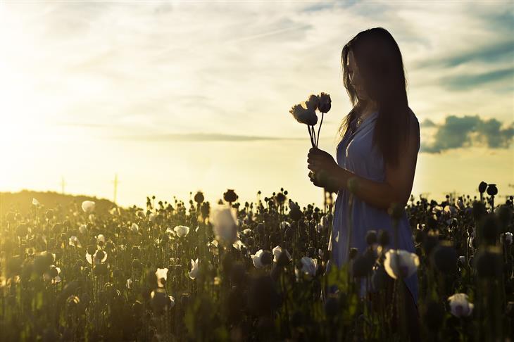 התבוננות עצמית בשיטת נאיקאן: אישה מחזיקה פרחים בשדה