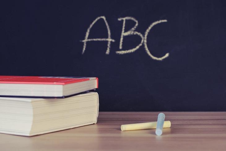 שיעורים לחיים: לוח בכיתה ושולחן שיש עליו ספרים וגירים