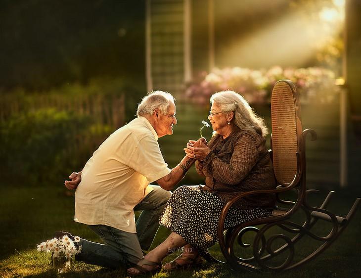 אהבה בגיל מבוגר: גבר מבוגר כורע על ברך ומגיש לאישה מבוגרת פרח
