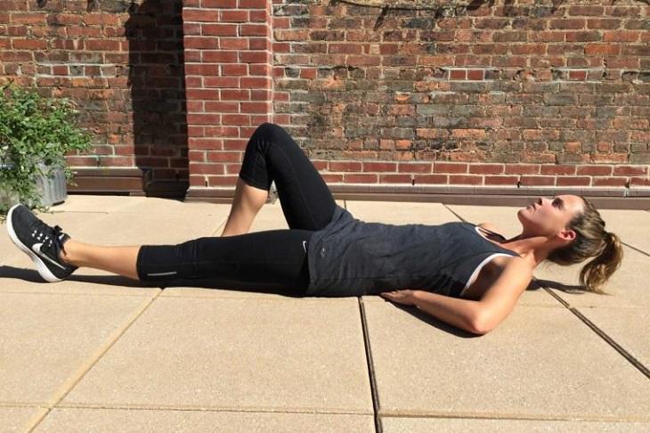 תרגילי כושר לבטן: בחורה שוכבת על הרצפה עם רגל אחת מכופפת וידיים מתחת לגב