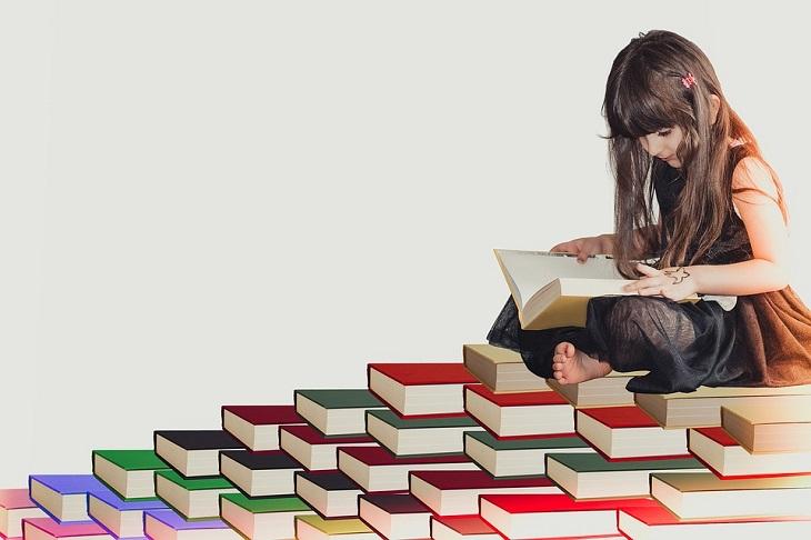 היריון בגיל מבוגר: ילדה קוראת ספר על פירמידת ספרים
