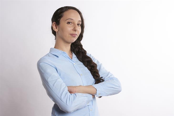 פעולות שפוגעות בביטחון העצמי: אישה משלבת ידיים ומביטה בבטחון במצלמה