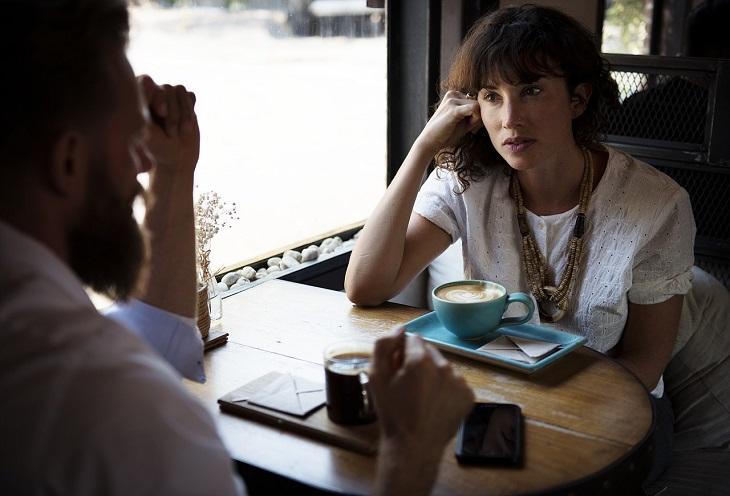 פעולות שפוגעות בביטחון העצמי: אישה יושבת עם גבר והם משוחחים