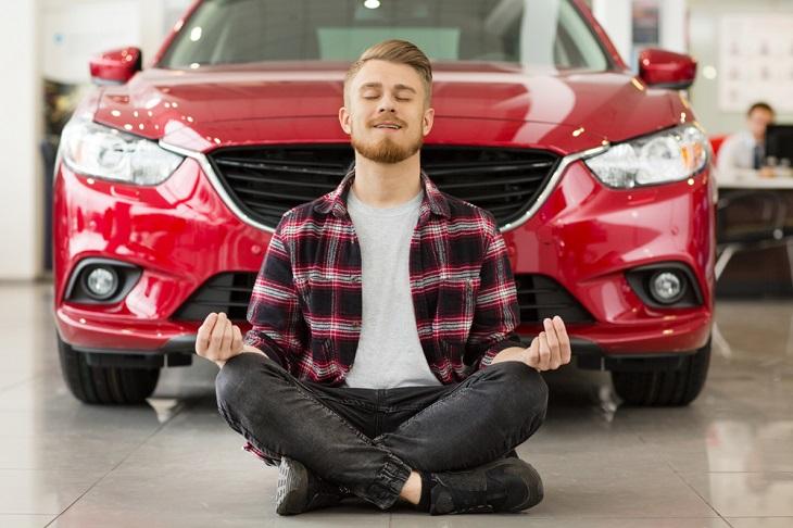 ביטוח לרכב: אדם צעיר יושב מול מכונית