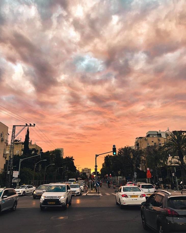 תמונות של תל אביב: מכוניות נוסעות ברחוב בזמן שקיעה