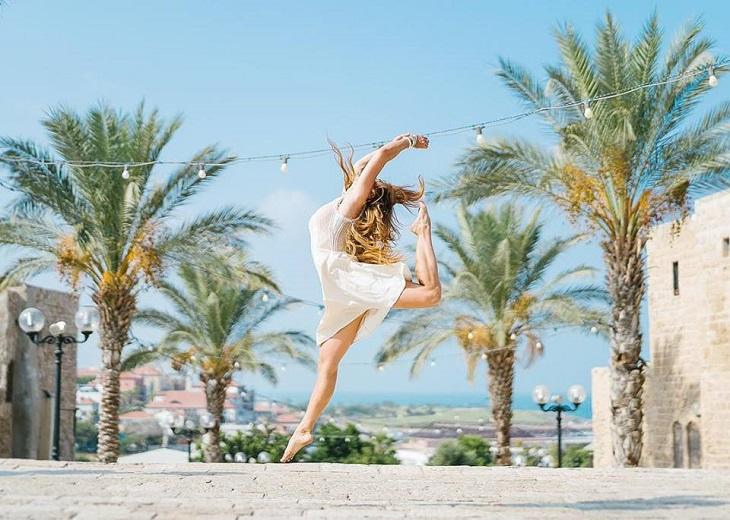 תמונות של תל אביב: בחורה רוקדת על רקע דקלים ביפו