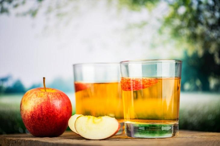 תרופות סבתא נגד כאבי בטן: שתי כוסות של חומץ סיידר תפוחים ולצידם תפוח ושני פלחים על שולחן