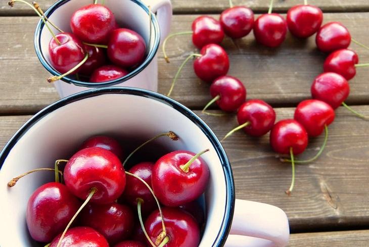 תרופות סבתא נגד כאבי בטן: שתי קערות של דובדבנים, ודובדבנים מסודרים בצורת לב על שולחן