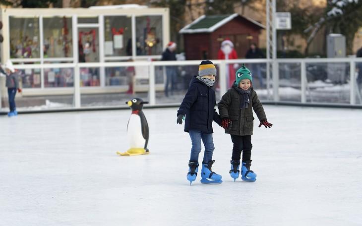 איך לגדל ילדים שיאהבו ללמוד: שני ילדים אוחזים ידיים ומחליקים על קרח