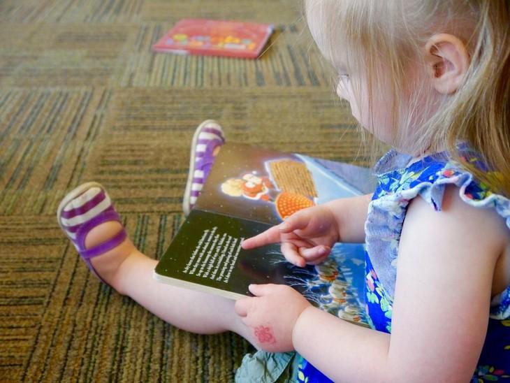 איך לגדל ילדים שיאהבו ללמוד: ילדה קטנה מצביעה על ספר
