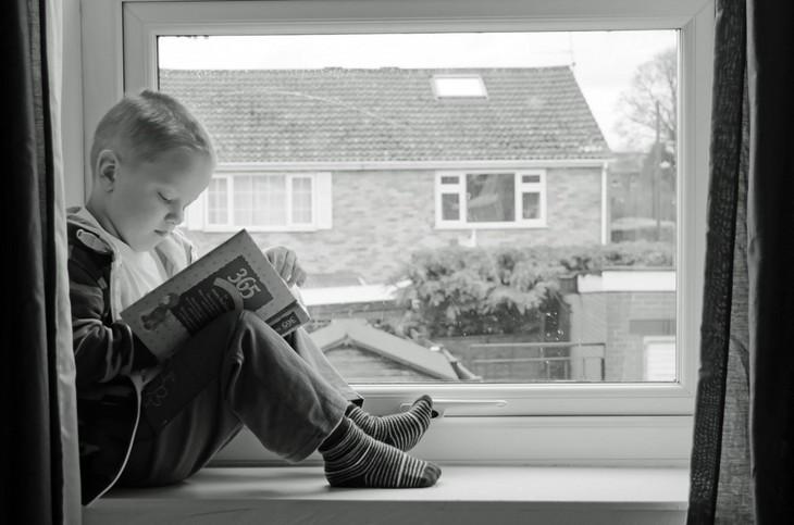 איך לגדל ילדים שיאהבו ללמוד: ילד יושב על אדן החלון וקורא ספר