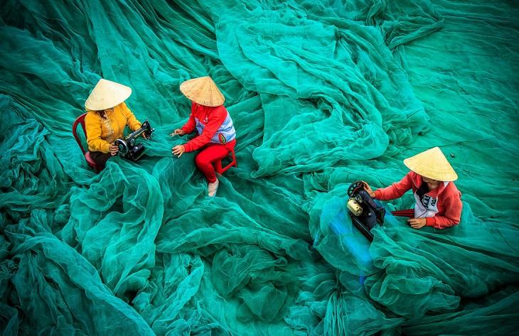 תמונות של מקומות עבודה: נשים מתקנות רשתות בווייטנאם