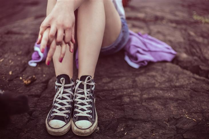 טיפים להורים עם נערים: נערה יושבת על רצפה ומשלבת את אצבעות ידיה