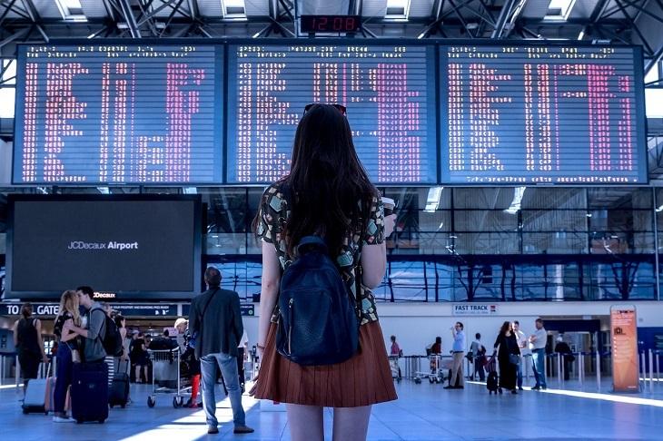 עצות פשוטות לחיים פשוטים: אישה עומדת עם תיק קל לפני לוח הטיסות בשדה תעופה