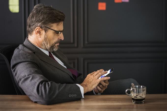 בחן את עצמך: איש בחליפה מתעסק בסמארטפון