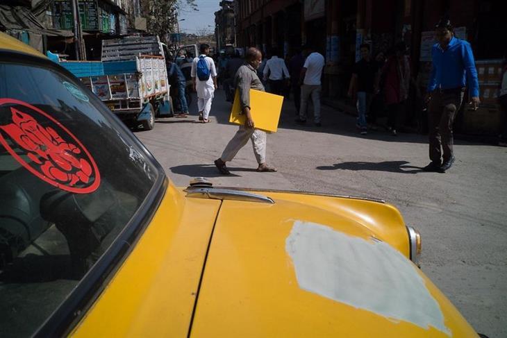 תמונות של צלם רחוב: גבר הולך עם לוח צהוב ליד מכונית צהובה עם חלק חסר