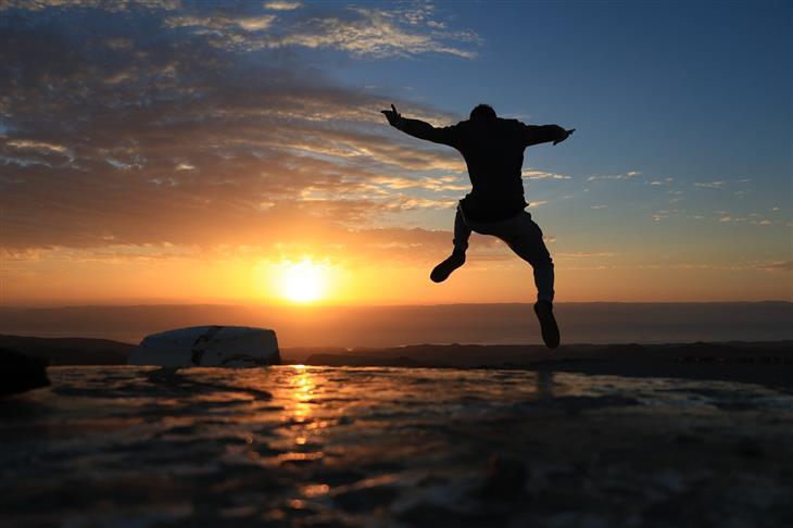 הוכחות לכך שאתם יותר עשירים ומבורכים ממה שחשבתם: צללית של איש קופץ מול שקיעה