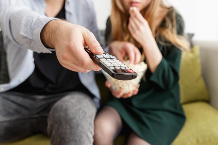 סרטים רומנטיים: זוג רואה טלוויזיה ואוכל פופקורן