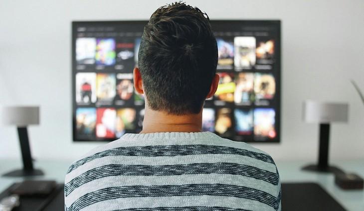 אפליקציות שלטים אוניברסליים: גבר יושב מול טלוויזיה