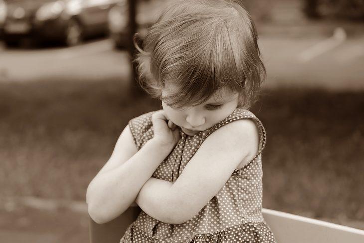 משפטים שעוזרים להרגיע ילדים: ילדה משלבת ידיים ומצמידה את הסנטר לחזה שלה