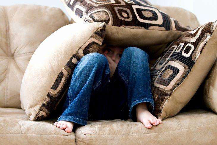 משפטים שעוזרים להרגיע ילדים: ילד מסתתר בין כריות ספה