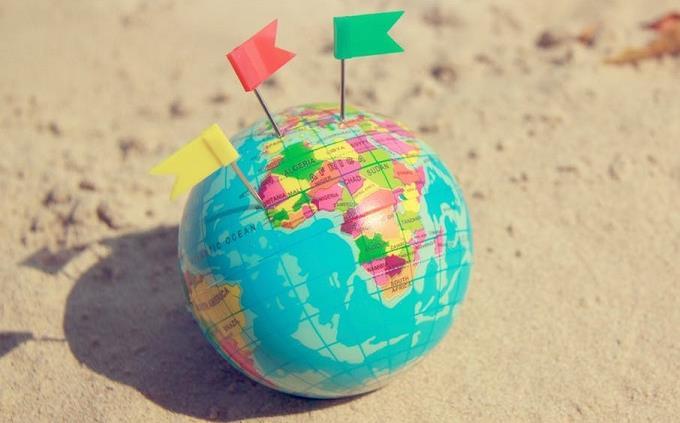 טריוויית הכרת הארץ: כדור גלובוס קטן עם דגלונים, מונח על חול