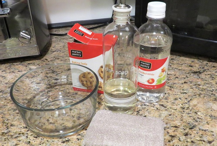 ניקוי תנור: קופסה של סודה לשתייה, בקבוקי חומץ ומים, קערה וכרית קרצוף על שיש