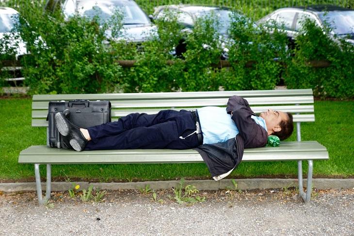 סימנים למחסור בוויטמין C: איש ישן על ספסל עם תיק עבודה לצידו