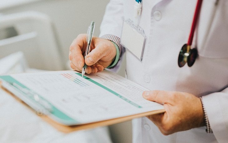 זכויות רפואיות בביטוח לאומי: רופא רושם על דף