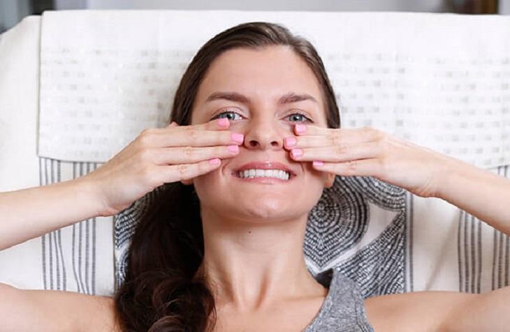 עיסויים לפנים: בחורה מחזיקה את כפות הידיים בזווית אופקית על הלחיים