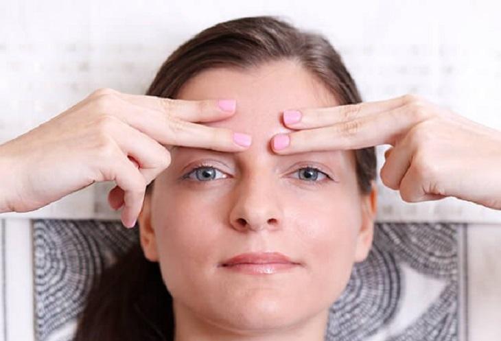 עיסויים לפנים: אישה מניחה אצבעות על המצח