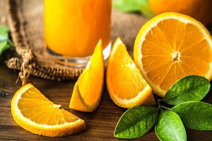 סימנים למחסור בוויטמין C: פלחים של תפוזים, לצד כוס מיץ ועלים על שולחן
