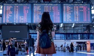 שאלון אישיות - מהי ציפור הנפש שלך: אישה עומדת מול לוח טיסות בשדה תעופה