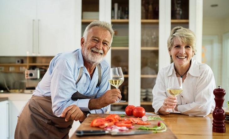 מחקר על זוגיות מאושרת: זוג מבוגר מחזיק כוסות יין במטבח ומחייך
