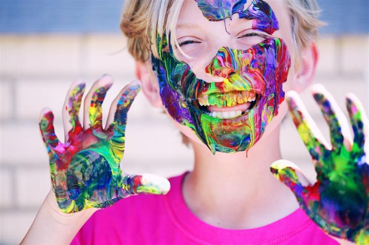 פסטיבל לא לדאוגוסט 2019: ילד מחייך, כשמרוחים צבעים על פניו וכפות ידיו