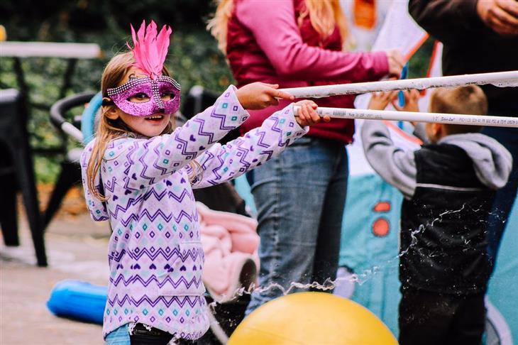 פסטיבל לא לדאוגוסט 2019: ילדה עם מסכה על הפנים משחקת בפסטיבל