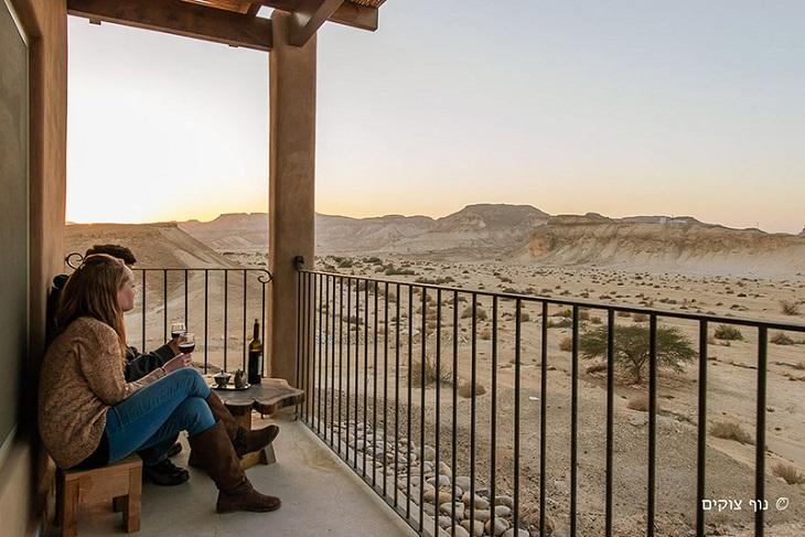 צימרים בדרום: זוג יושב על מרפסת מול נופי מדבר