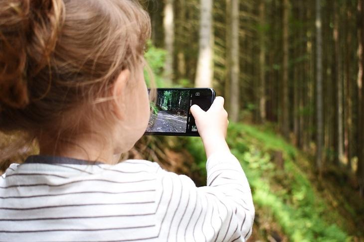 דברים שהורים צריכים לגרום לילדים להפסיק לעשות: ילדה מתבוננת במסך סמארטפון