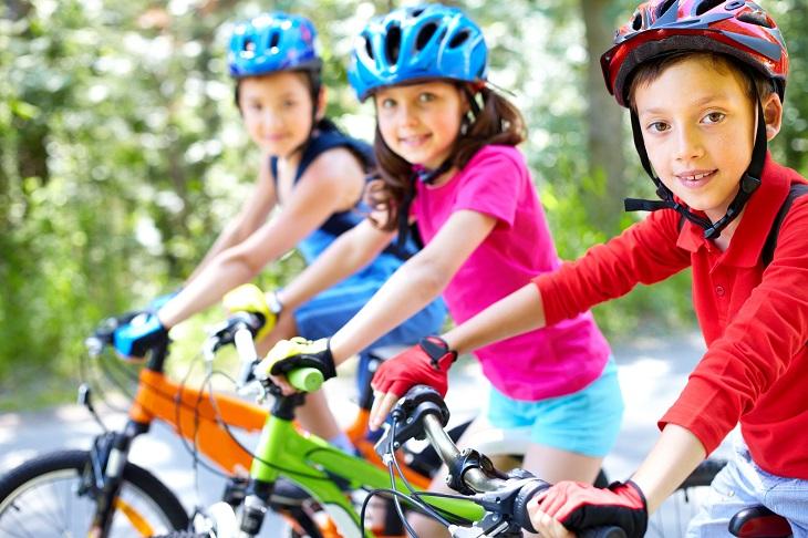 דברים שהורים צריכים לגרום לילדים להפסיק לעשות: ילדים על אופניים עם קסדה