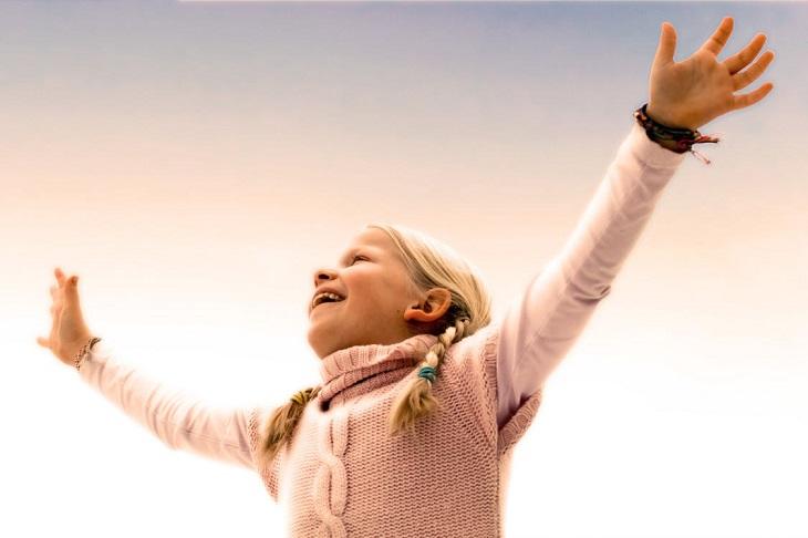 טיפים של מורים להורות: ילדה מחייכת ומרימה ידיים
